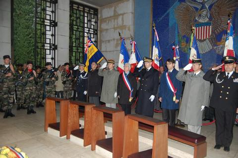 Participants salute in the chapel in front of a mosaic wall during the 2012 Veterans Day ceremony at Rhone American Cemetery.