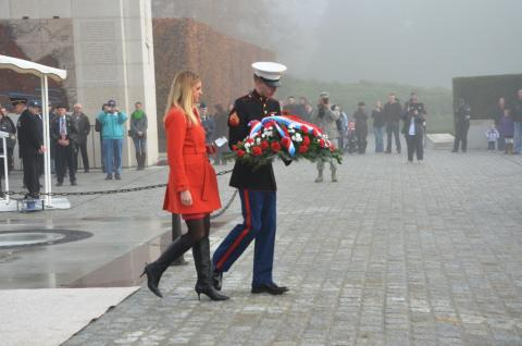 ABMC Commissioner Maura Sullivan walks with a marine holding a floral wreath.