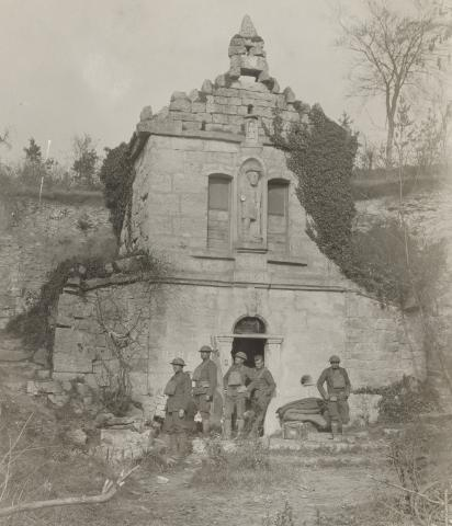 Historic photo shows soldiers standing in front of brick monument.