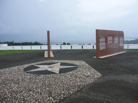 Two of the marble walls of the memorial are seen at an angle. Water is visible in the distance.