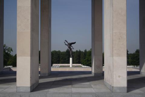 An angel statue viewed through the columns of the Henri-Chapelle American Cemetery memorial building.