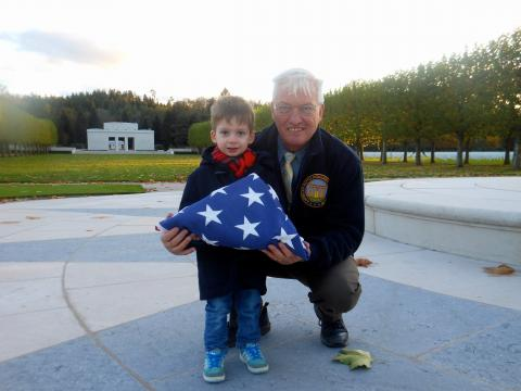 Aaron Howson and Superintendent Anderson stand with folded flag.