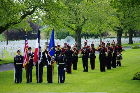 American honor guard stands with a French military band in background.