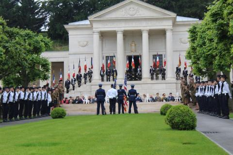 Flag bearers and men and women in uniform stand in front of the memorial building during the ceremony.