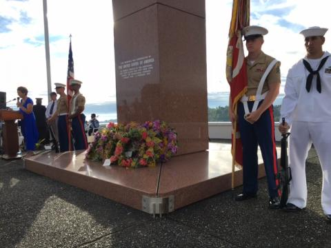 Three Marines and a sailor stand next to the granite memorial.