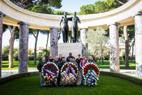 Men and women in motorcycle gear stand behind large floral wreaths after the ceremony.