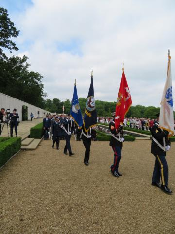 Members of the American military carry the service flags during the ceremony.