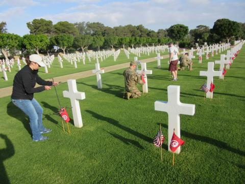 Volunteers place an American flag and Tunisian flag in front of every headstone.