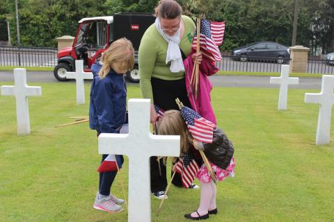 A woman and two children help to place the American and French flags in front of a headstone.