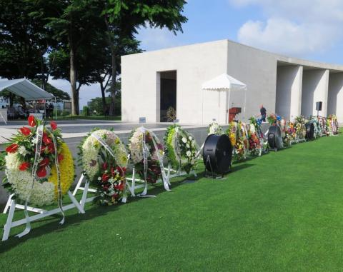 Floral wreaths on stands rest near the Walls of the Missing.