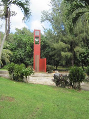 Amidst greenery, a memorial area includes a granite column.