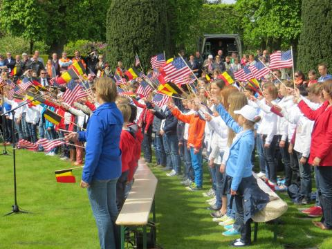 Rows of school children wave American and Belgian flags.