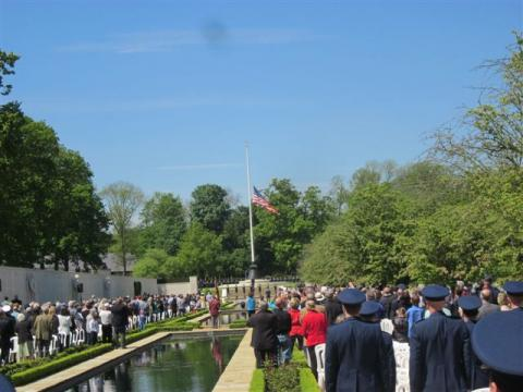 Attendees stand around reflecting pool, facing flag pole with flag at half mast.