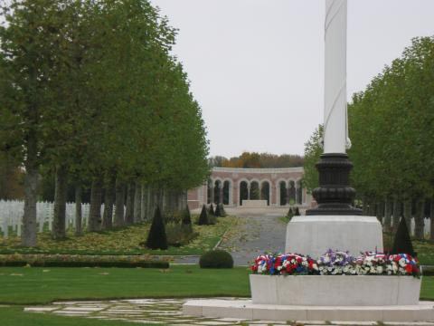 Wreaths lie at the base of a flag pole, with headstones and the chapel in the background, at Oise-Aisne American Cemetery for the 2012 Veterans Day ceremony.