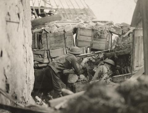 Historic photo shows soldiers firing a rifle.
