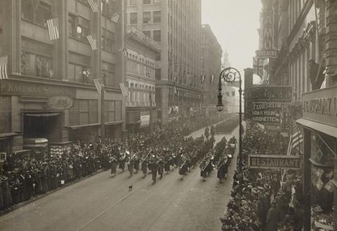 Historic photos shows men in uniform parading down city street.