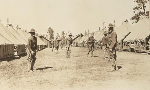 Historic photo shows soldiers in uniform standing near large tents.