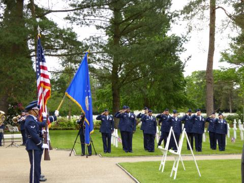 Airmen salute while the Color Guard posts the colors.