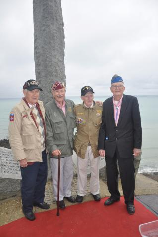 Four World War II veterans stand in front of the Ranger Monument at Pointe du Hoc.