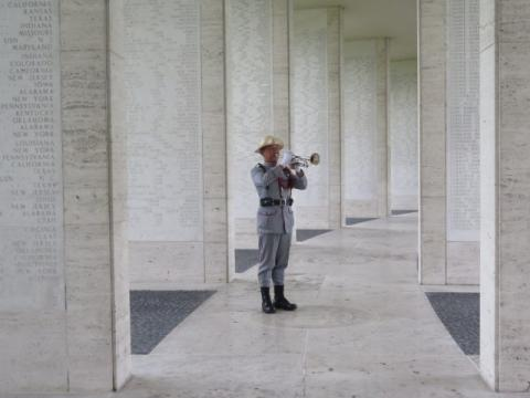 A man in uniform plays the bugle amidst the Walls of the Missing.