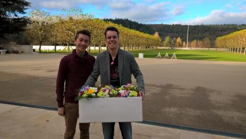 Two men stand with a box filled with flowers, ready to place them at gravesites.