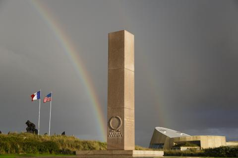 A double rainbow appears in the sky behind the memorial.