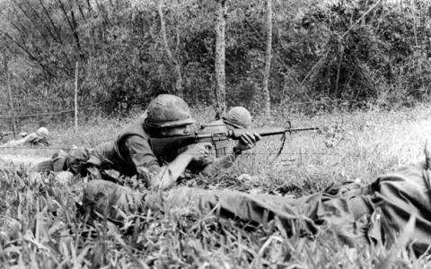 Historic photo shows a man firing a weapon.