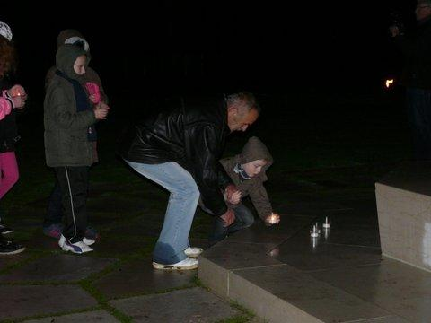 A man and child place candles at the base of the flag pole.