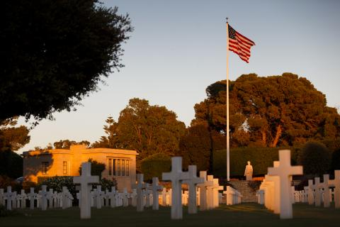 Headstones, the American flag and the memorial building at North Africa American Cemetery.